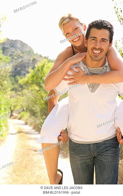 Man carrying girlfriend piggyback on dirt path
