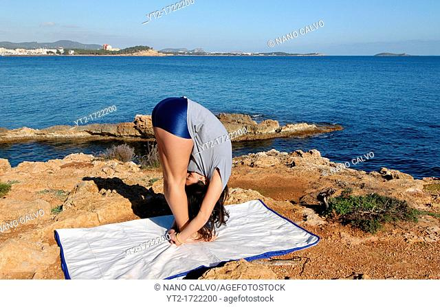 Young female doing yoga on cliff