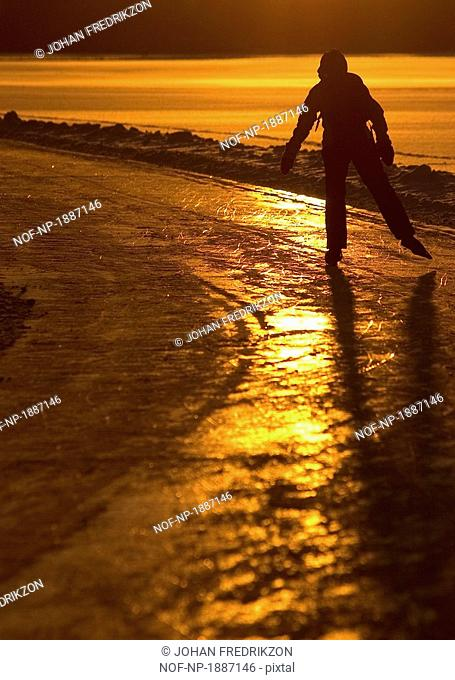 A person seems to be skating directly into the afternoon sun on the ices of a Stockholm lake