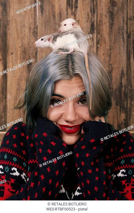 Portrait of smiling young woman with two pet rats on her head wearing patterned knit pullover