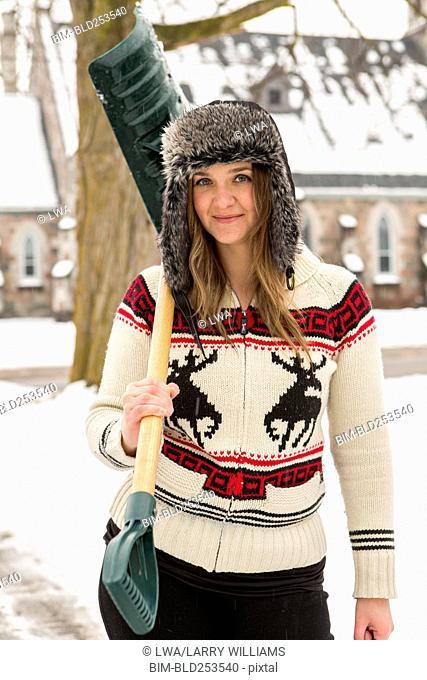 Portrait of Caucasian woman carrying snow shovel