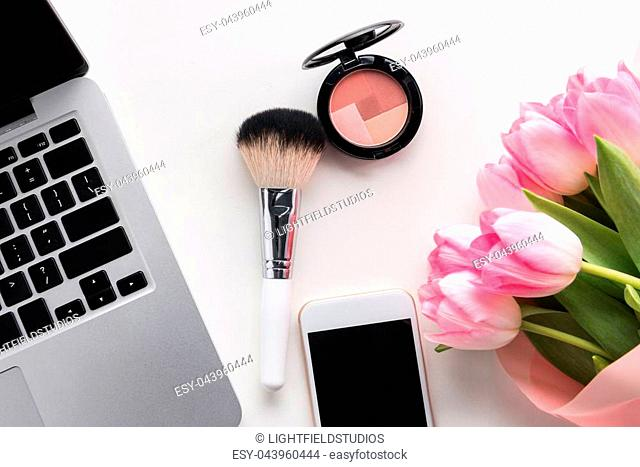Flat lay of open laptop, smartphone with blank screen, flowers and makeup brush isolated on white