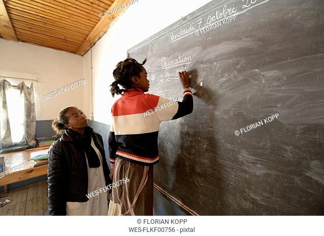 Madagaskar, Girl in Fianarantsoa elementary school calculatiing at blackboard