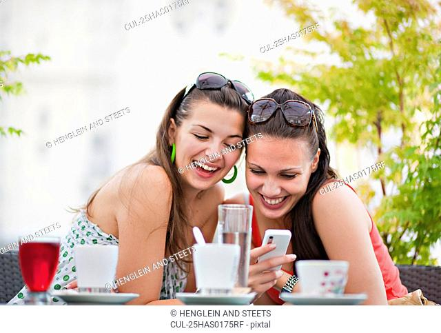 Young women looking at phone in cafÈ
