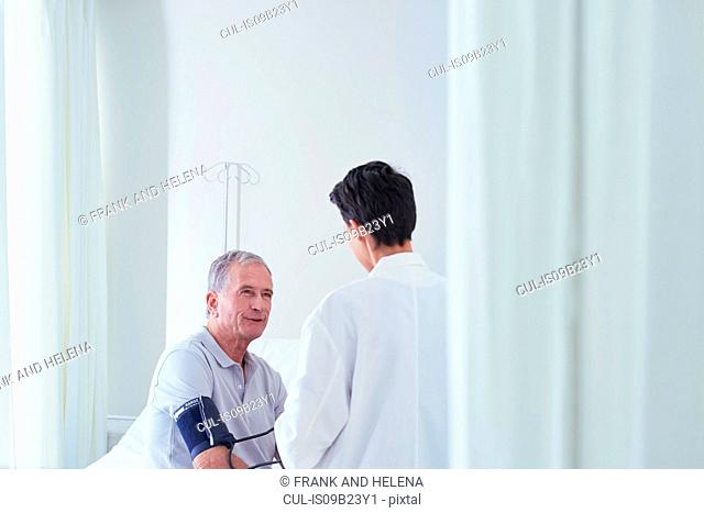 Senior male patient having blood pressure blood pressure gauge taken by female doctor