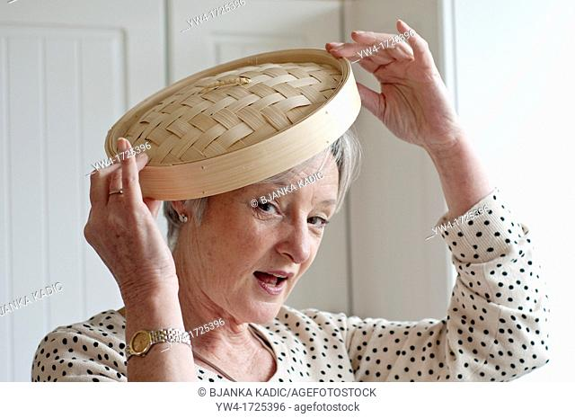 Middle aged woman playing with bamboo lid in kitchen