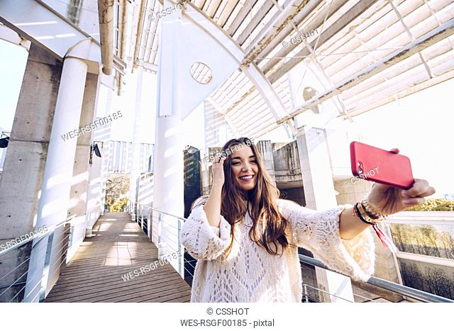 Happy young woman taking a selfie on a bridge