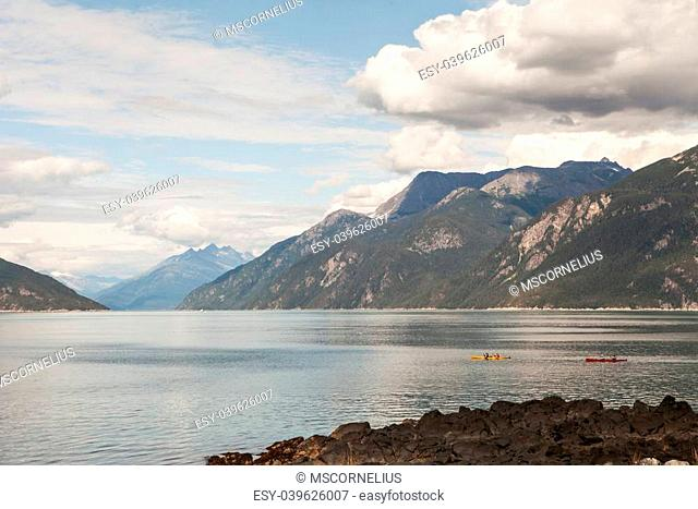 Two double kayaks in Portage Cove near Haines in Southeast Alaska on a summer day with clouds