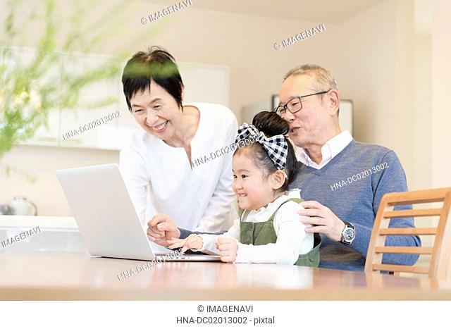 Grandparents and grandchild playing with laptop
