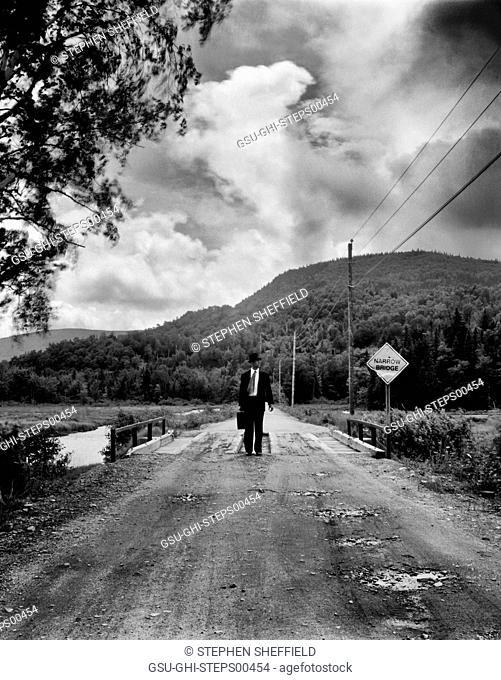 Mid-Adult Businessman Walking across Narrow Rural Bridge