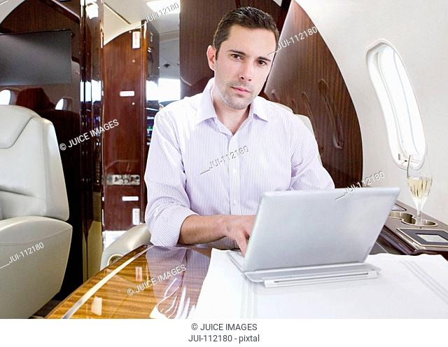 Man looking at camera working on digital tablet on private jet