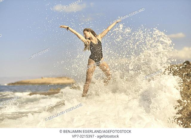young woman stretching arms at seaside enjoying summer holiday, sunny weather and freedom, refreshing water splashes, in Crete, Greece