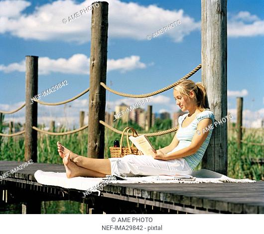 A woman sitting on a wooden bridge reading a book