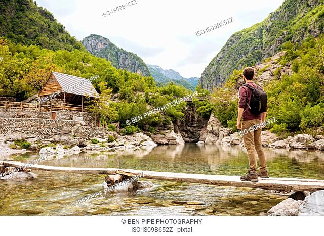 Man on wooden bridge looking at cabin, Accursed mountains, Theth, Shkoder, Albania, Europe