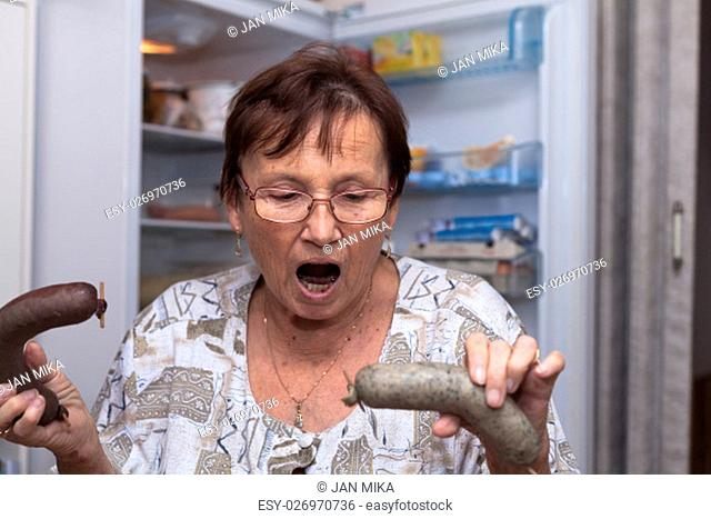 Shocked senior woman holding pork liver sausages while standing in front of the open fridge in the kitchen
