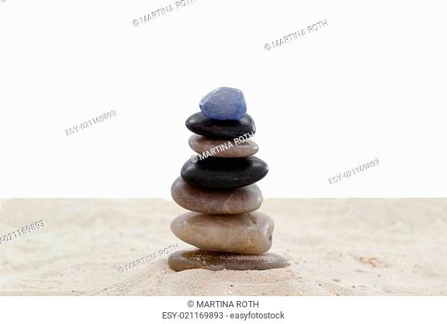 Balanced pebbles on sand