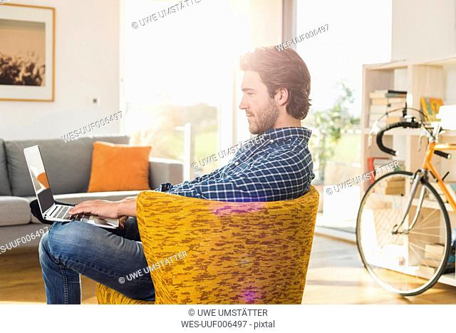 Young man sitting on an armchair in the living room using laptop