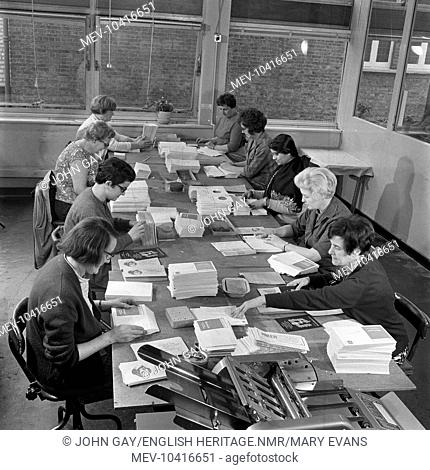 A group of women seated at a long table placing leaflets in envelopes in the premises of the Medical Mailing Company