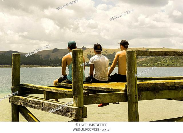 Back view of three friends sitting on a jetty