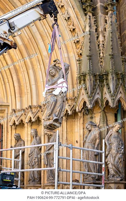 "24 June 2019, Thuringia, Erfurt: A sculpture of the """"foolish virgins"""" is dismantled with the help of a crane at the beginning of the renovation of the..."