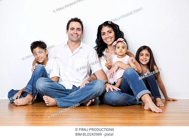 Portrait of smiling Mixed Race family sitting on floor