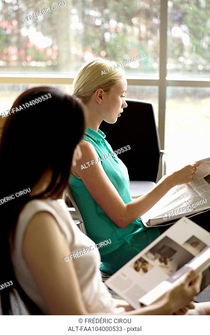 Women reading to kill time in waiting room