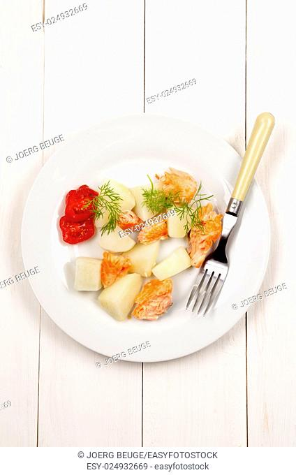 boiled potatoes with fried salmon, tomatoes and dill on a white plate