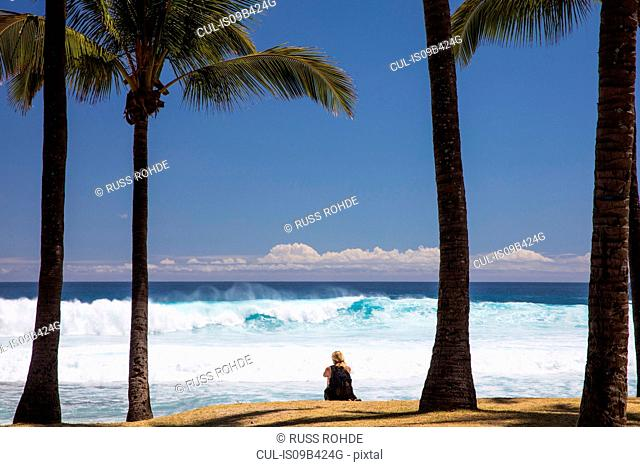 Female tourist sitting on beach looking out at Indian Ocean, Reunion Island