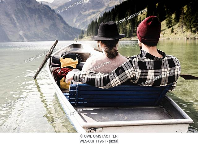 Austria, Tyrol, Alps, relaxed couple in rowing boat on mountain lake