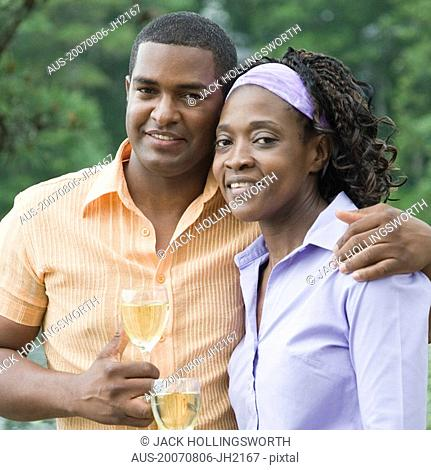 Portrait of a mature man and a mid adult woman holding glasses of wine and smiling