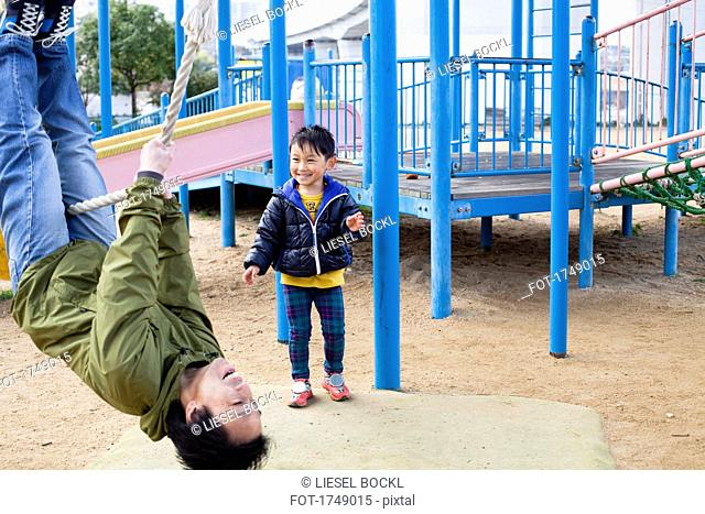 Smiling boy looking at father swinging on rope in playground