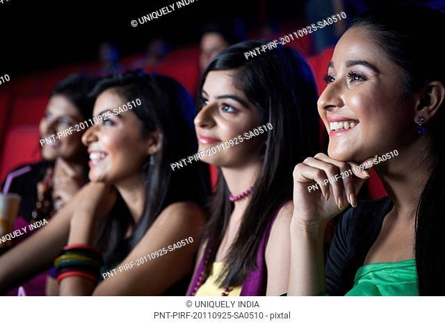 Female friends enjoying movie in a cinema hall