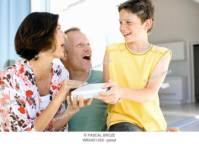 Close-up of a boy giving a gift to his parents