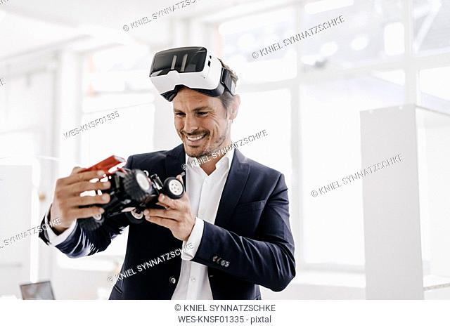 Smiling businessman wearing VR glasses looking at toy racing car