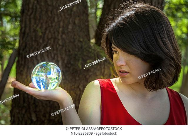 Young woman, standing by a tree in a park, holding a crystal ball