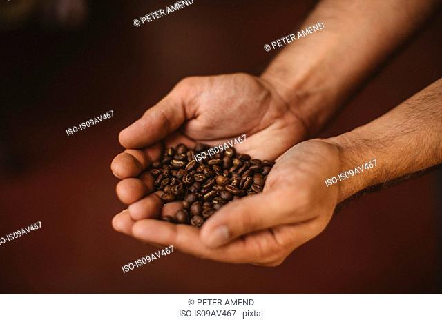 Man holding coffee beans, close-up