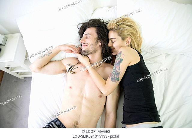 A cool young tattooed couple cuddling on a bed
