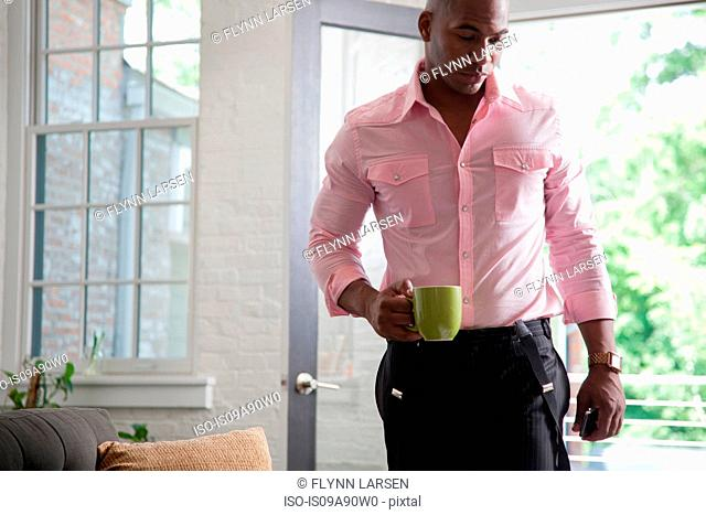 Mid adult man holding mug at home
