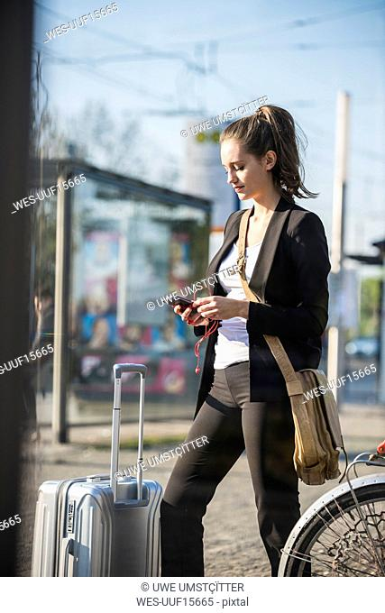 Young woman with luggage at tram station in the city checking cell phone
