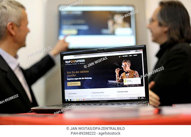 A man explains the talent platform MyPoolitzer displayed on a laptop at the Leipzig Book Fair in Leipzig, Germany, 24 March 2017