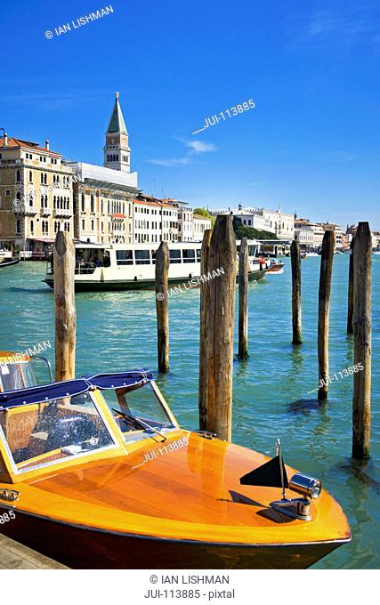 Water taxi and moored boat on sunny Grand Canal in front of San Marco Campanile and architectural buildings in Venice, Italy