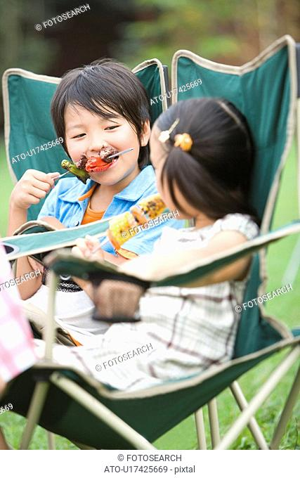 Boy and girl biting on kebabs, differential focus