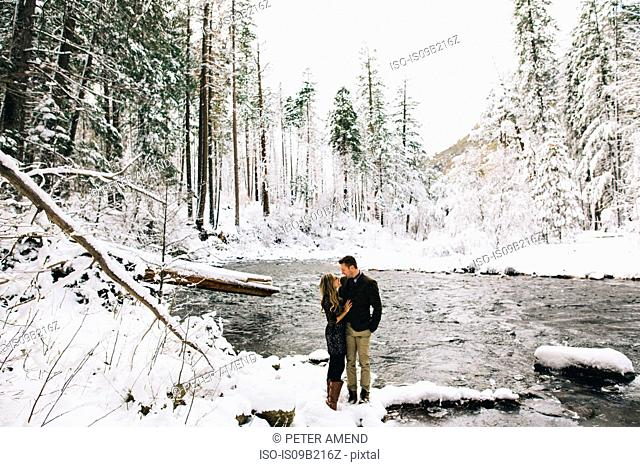 Couple in snow-covered forest by river face to face smiling