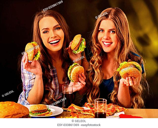 Two happy girls bite burger with two sides. Fastfood concept
