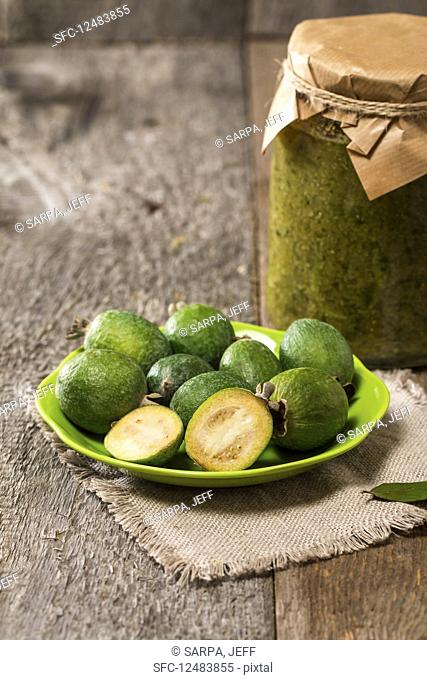 Fresh fruits of feijoa in a bowl and feijoa jam on wooden table