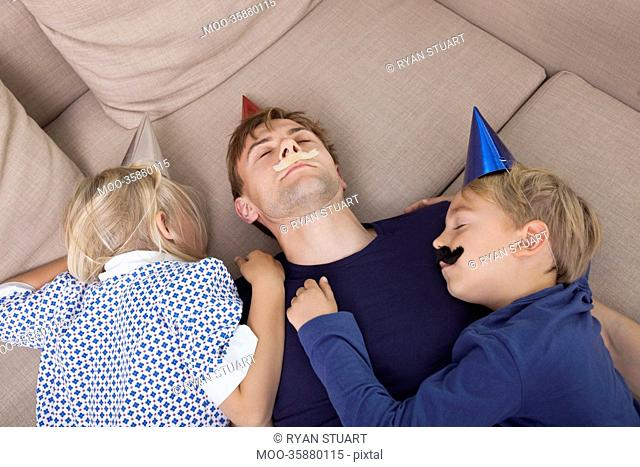 High angle view of children and father with artificial mustache and party hat sleeping on sofa bed