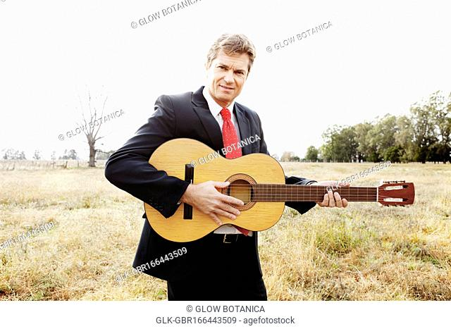 Businessman playing a guitar in a field