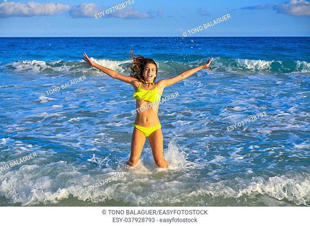 Bikini teen girl jumping happyt in Caribbean sunset beach splashing shore