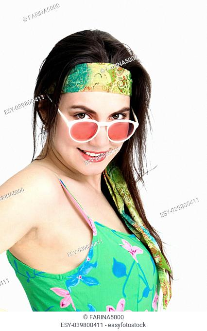 Sexy woman wearing a headband tilting her head and looking over the top of her rose coloured glasses with a smile isolated on white
