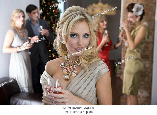 Portrait of sexy blonde woman having a glass of wine at holiday party with friends